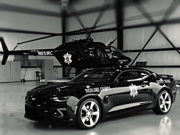 Black and white photo of RCSD helicopter and Chevy Camaro