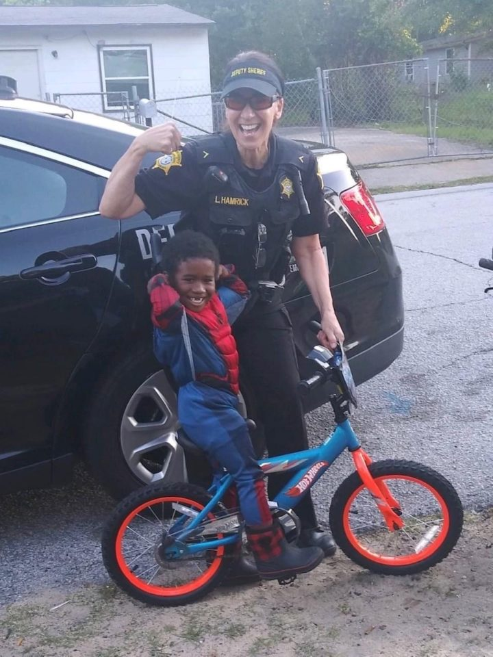 Deputy with small boy on a bicycle.