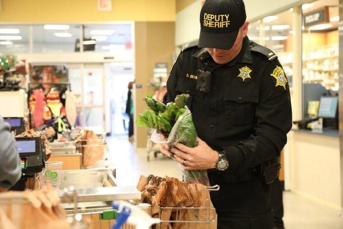 Deputy bagging groceries at supermarket